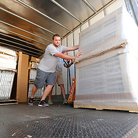 Thomas Wells | Buy at PHOTOS.DJOURNAL.COM<br /> Aaron Williams, left, and Chad Smith continue to push pallets of new office furniture to the rear of the trailer so it can be offloaded and assembled at the new Tupelo Police Headquarters on Front Street Monday.