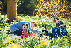 Happy Family Sitting in Garden