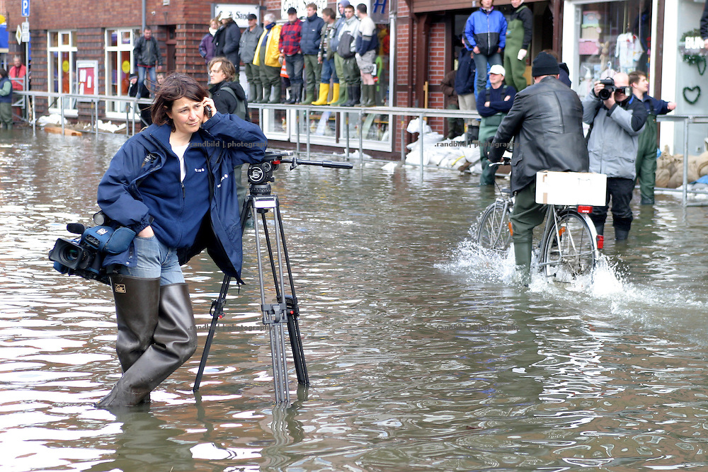 Eine Kamerafrau steht im überfluteten Hitzacker und stützt sich telefonierend auf ihr Stativ...A journlaist stands in the floods in Hitzacker.