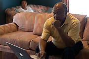Johnny Lewis looks up photographs for his wife, Shirley, at their home in Fort Worth, Texas on April 21, 2014. Johnny is the caretaker for Shirley who has been diagnosed with ALS. (Cooper Neill / for AARP)