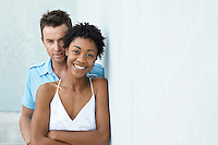Couple standing together against wall portrait