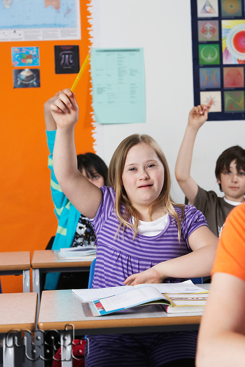 Girl (10-12) with Down syndrome raising hand in classroom