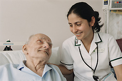 Female occupational therapist smiling at elderly patient,