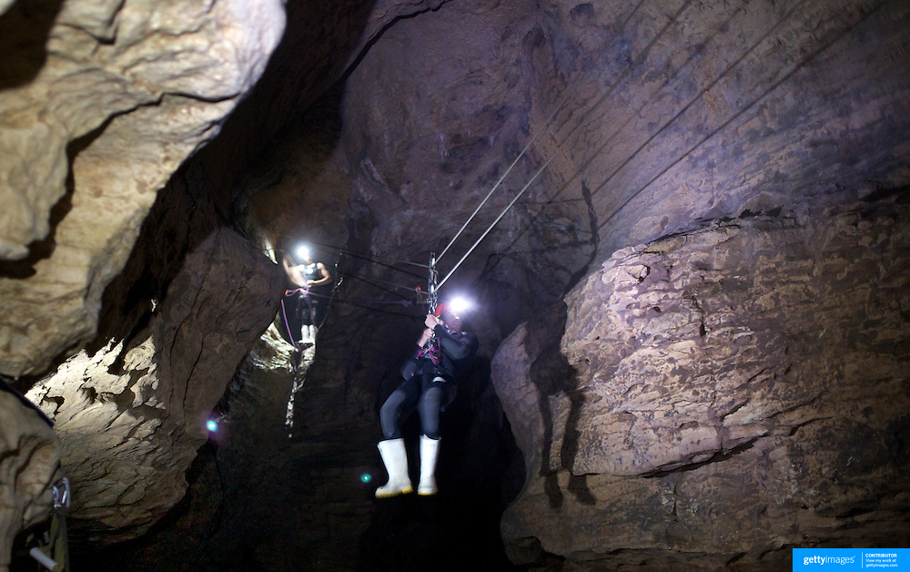 A participant travels along a flying fox while entering the Ruakuri Cave while Black Water rafting in the Waitomo Glowworm Caves, Waitomo, North Island, New Zealand..The Legendary Black Water Rafting Company is New Zealand's first black water adventure tour operator which takes tourists through the  Ruakuri Cave at Waitomo..The five hour expedition combines abseiling the 35 metre entrance. climbing, a flying fox. black water tubing, leaping and floating through Ruakuri Cave and observing glow worms. The journey concludes  into the sunlight of the Waitomo forest..Waitomo, New Zealand,, 14th December  2010 Photo Tim Clayton