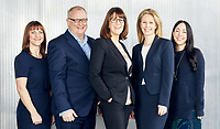 Corporate groups shot featuring small team of lawyers taken outdoors with modern grey striped background