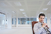 Office worker sitting in swivel chair hands clasped in empty office space