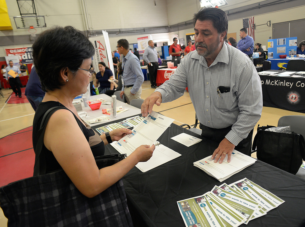apl071917g/ASECTION/pierre-louis/JOURNAL 071917<br /> Lea Crisostomo,, left goes over the employment application process with ABQ Ride Senior Personnel Victor Lovato,, during the Job Fair held at Harrison Middle School .  94 employers conducted interviews and job screening for more than 4,000 job seekers .Photographed on Wednesday July  19,  2017. .Adolphe Pierre-Louis/JOURNAL
