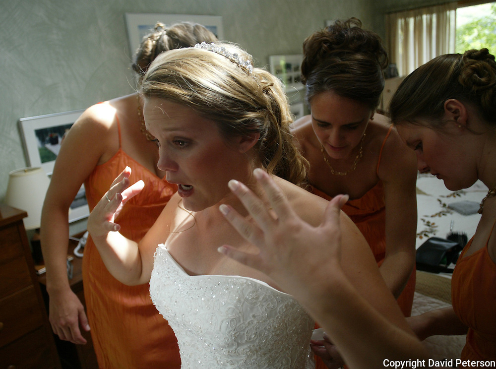 Young bride Leaf Sackington, experiences a nervous moment as she prepares for her big day.  Her bridesmaids work on last minute adjustments to her wedding dress. From right are sister Meadow Stoner and bridesmaid Julie Zimmer. She was married near Iowa City, Iowa.