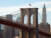 A pillar of the Brooklyn Bridge with the Woolworth building in the background.