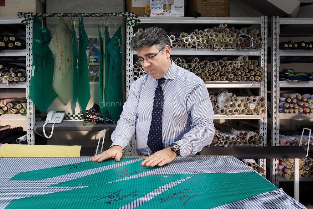 ARZANO, ITALY - 16 January 2014: Supervisor of the tie division places models on a fabric used for a tie, at the Kiton factory in Arzano, Italy, on January 16th 2014.