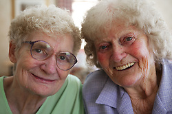 A couple of elderly women friends smiling and laughing,