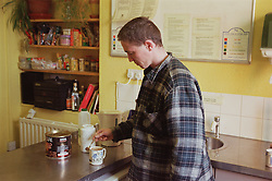 Male resident of homeless hostel for people with learning difficulties making cup of coffee in communal kitchen,