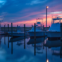 A colorful, twilight sky accentuates boats docked in the Frisco Harbor, Cape Hatteras National Seashore, NC