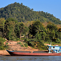 Logs Staged for Cargo Ship on Mekong River in Luang Prabang, Laos <br />