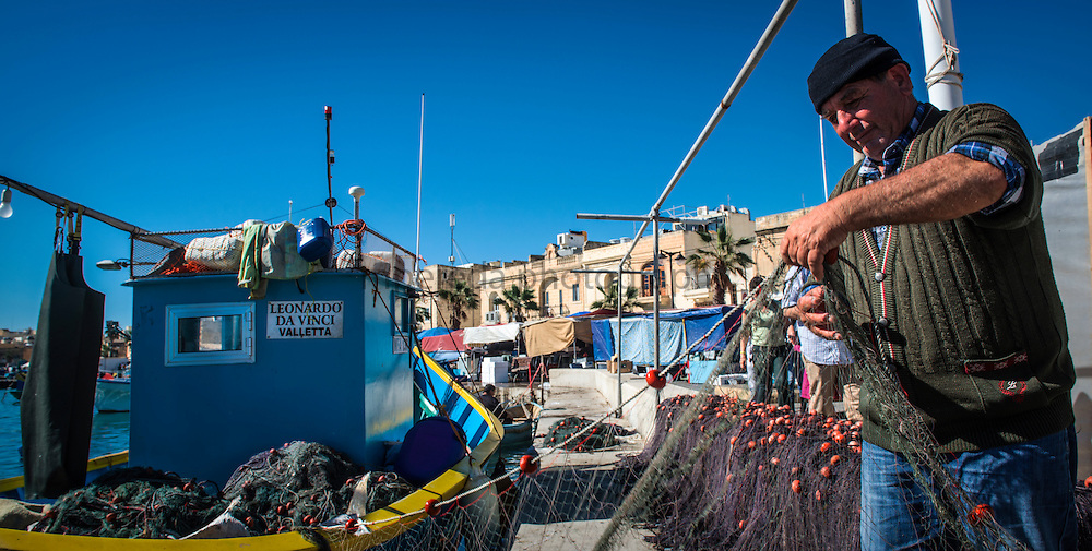 Fisherman working along his boat at Marsaxlokk's harbour.