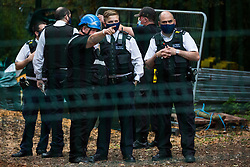 A National Eviction Team enforcement agent speaks to Metropolitan Police officers from within a compound used to fell trees as part of works connected to the HS2 high-speed rail link in Denham Country Park on 7 September 2020 in Denham, United Kingdom. Anti-HS2 activists continue to try to prevent or delay works on the controversial £106bn project for which the construction phase was announced on 4th September from a series of protection camps based along the route of the line between London and Birmingham.