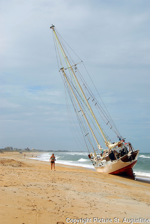 High and Dry. A woman walks past a 65 foot Schooner Sail Boat which ran aground on Vilano Beach, Florida. The schooner came ashore when the Captain attempted to negotiate the St. Augustine Inlet  during the build up to Tropical Storm Fay. Later that night the sail boat broke apart in high winds and surf.