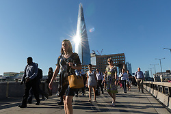 © Licensed to London News Pictures. 03/08/2018. London, UK.  Commuters walk to work across London Bridge as bright sunlight reflects on the London Shard during another day of hot and sunny weather, as the heatwave returns to London.  Photo credit: Vickie Flores/LNP