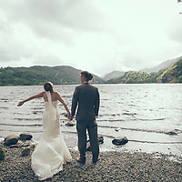 Wedding day with bride and groom standing in country scene in England beside lake