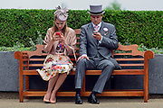 © London News Pictures. 20/06/2013. Ascot, UK. A couple look at there mobile phones on a bench. Ladies Day on day three of Royal Ascot at Ascot racecourse in Berkshire, on June 20, 2013. The 5 day showcase event, which is one of the highlights of the racing calendar, has been held at the famous Berkshire course since 1711 and tradition is a hallmark of the meeting. Top hats and tails remain compulsory in parts of the course.  Photo credit : Stephen Simpson/LNP