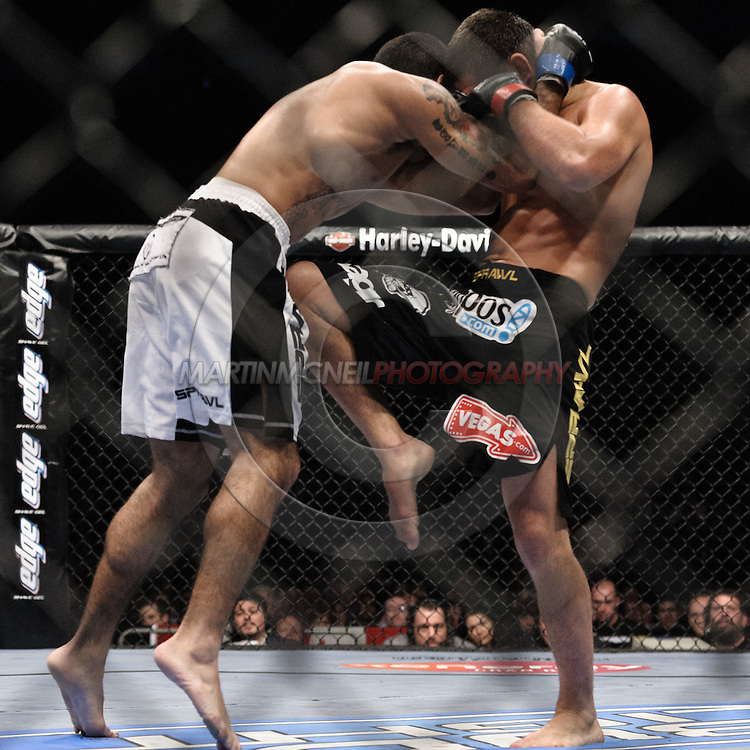 """LONDON, ENGLAND, JUNE 7, 2008: Thiago Tavares (left) slips back from a knee strike thrown by Matt Wiman during """"UFC 85: Bedlam"""" inside the O2 Arena in Greenwich, London on June 7, 2008."""
