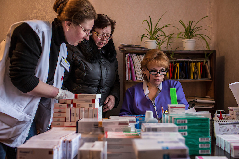 ZIMOGORYE, UKRAINE - MARCH 15, 2015: Lidia Grishko, left, a physician with Medecins Sans Frontieres, and Venera Lukyanchenko, right, a general practitioner at the Zimogoryivskaya Ambulatory, consult with a patient in Zimogorye, Ukraine. CREDIT: Brendan Hoffman for The New York Times