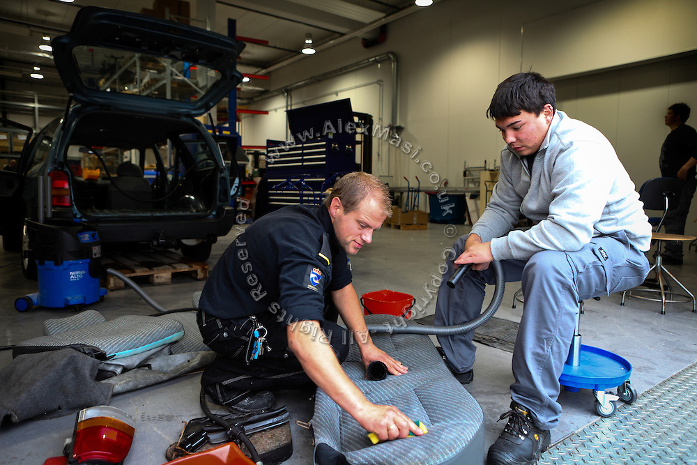 A guard (left) is teaching car-repairing and basic mechanics to attentive inmate inside the luxurious Halden Fengsel, (prison) near Oslo, Norway.
