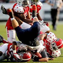 Jan 26, 2013; Mobile, AL, USA; Senior Bowl north squad offensive lineman Justin Pugh of Syracuse (67) is tackled after picking up a fumble by Senior Bowl south squad defensive back Robert Lester of Alabama (37) and defensive lineman Cornelius Washington of Georgia during the first half of the Senior Bowl at Ladd-Peebles Stadium. Mandatory Credit: Derick E. Hingle-USA TODAY Sports