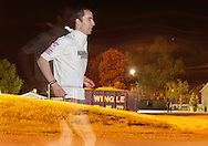 Augusta, New Jersey - The light from a camera's flash illuminates Byron Lane, the evenutal second-place finisher in the 24-hour race, as he runs in the 3 Days at the Fair races at the Sussex County Fairgrounds on the night of May 16, 2010. The fireworks in the background were from a carnival at Skylands Park.