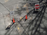 Looking down on street signs, two pylons, and shadows on the pavement of a road in Central Park.