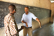 Calvin Doe (right), Youth Ambassador for The Kraft Cocoa Partnership talking to Daniel one of the teachers at the Mbaem community school n the eastern region of Ghana.