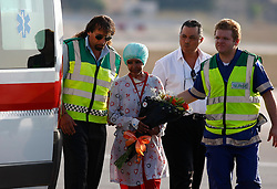 Shwejga Mullah (2nd L) of Ethiopia is helped to a waiting ambulance after arriving at Malta International Airport,outside Valletta September 15, 2011. An Ethiopian nanny in the Gaddafi household who suffered horrific burns after she did not stop one of Muammar Gaddafi's grandchildren crying, has arrived in Malta for specialised medical treatment. Shwejga Mullah was recently discovered weak and alone in the home abandoned by Muammar Gaddafi's son Hannibal. She said that  Hannibal Gaddafi's wife Aline threw boiling water over her when she did not stop Hannibal Gaddafi's daughter crying and refused to beat the child. The nanny was brought over in a private plane chartered by the Maltese government.    REUTERS/Darrin Zammit Lupi (MALTA)