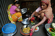 """Shahnaz Hossain Begum (left) shares cooking space with one of her tenants at her home in Bari Majlish village outside Dhaka, Bangladesh. (From the book What I Eat: Around the World in 80 Diets.)  The caloric value of her day's worth of food for a typical day in December was 2000 kcals. She is 38; 5' 2"""" and 130 pounds. This mother of four was able to earn enough to build several rental rooms next to her home in her village of Bari Majlish, an hour outside Dhaka. She and her tenants share a companionable outdoor cooking space and all largely cook traditional Bangladeshi foods such as dahl, ruti (also spelled roti), and vegetable curries. She and her family don't drink the milk that helps provide their income."""