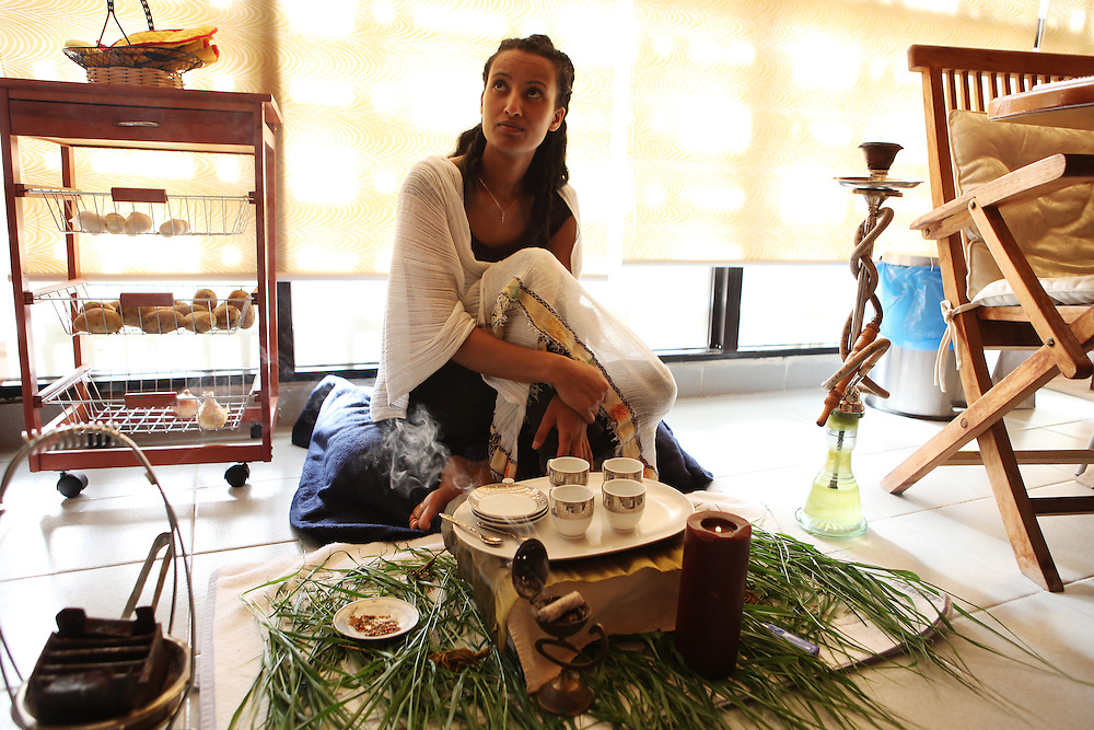 An Ethiopian woman waits to enjoy Ethiopian coffee and sweets with friends on their day off.