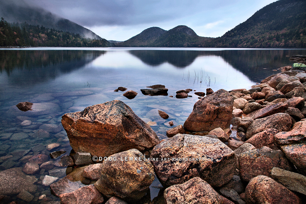 The Bubbles in the background and boulders in Jordan Pond on a cool autumn evening at Acadia National Park, Maine, USA