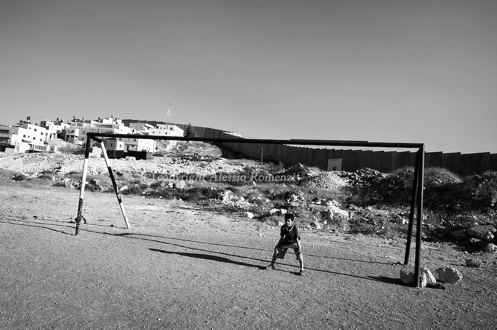 Young Palestinians plays at a football pitch next to controversial Israeli separation barrier in the West Bank village of Abu Dis, on the outskirts of Jerusalem on June 8, 2010.© ALESSIO ROMENZI