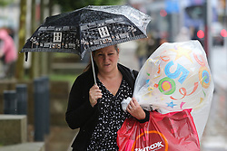 © Licensed to London News Pictures. 22/08/2016. Leeds, UK. A woman struggles with her bags and umbrella on a rainy and windy day in Leeds, West Yorkshire. Forecaster are predicting a heatwave this week, but it has started with rain, wind and no sunshine. Photo credit : Ian Hinchliffe/LNP
