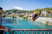 A man jumps in a backwards somersault from the Untertor Brucke in Bern. The Aare river floats right through the Swiss capital Bern, and as soon as the temperature crawls above 10 degrees, people are seen jumping in the water for a swim. Many use the river regularly to swim to lunch or to and from work. Some even swim year round.