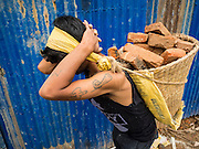31 JULY 2015 - KATHMANDU, NEPAL: Workers carry bricks and building materials to be recycled and reused out of a Buddhist monastery at Swayambhunath, also known as the Monkey Temple. Two monks were killed when the monastery was destroyed by the earthquake. Swayambhunath is a complex of Buddhist and Hindu temples in Kathmandu. It was heavily damaged in the Nepal Earthquake. The Nepal Earthquake on April 25, 2015, (also known as the Gorkha earthquake) killed more than 9,000 people and injured more than 23,000. It had a magnitude of 7.8. The epicenter was east of the district of Lamjung, and its hypocenter was at a depth of approximately 15km (9.3mi). It was the worst natural disaster to strike Nepal since the 1934 Nepal–Bihar earthquake. The earthquake triggered an avalanche on Mount Everest, killing at least 19. The earthquake also set off an avalanche in the Langtang valley, where 250 people were reported missing. Hundreds of thousands of people were made homeless with entire villages flattened across many districts of the country. Centuries-old buildings were destroyed at UNESCO World Heritage sites in the Kathmandu Valley, including some at the Kathmandu Durbar Square, the Patan Durbar Squar, the Bhaktapur Durbar Square, the Changu Narayan Temple and the Swayambhunath Stupa. Geophysicists and other experts had warned for decades that Nepal was vulnerable to a deadly earthquake, particularly because of its geology, urbanization, and architecture.        PHOTO BY JACK KURTZ