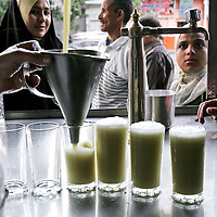 Customers look on as a worker pours sugar cane juice at the Saad Afifi Sons - Sugarcane Juice shop in Cairo, Egypt. The juice made from sugar cane sells for less than 10 cents each. May 2007.
