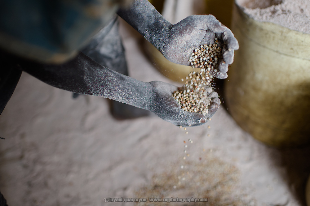 Emmanuel Ohisa, a young mill hand, scooping up sorghum that had fallen onto the floor at a mill in the village of Kudo in Eastern Equatoria in South Sudan on 8 August 2014.