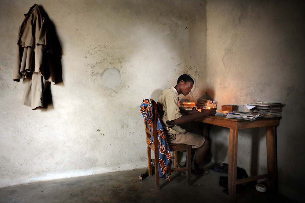 A teenager does his homework on a table in his bedroom in Cotonou, Benin February 29, 2008.
