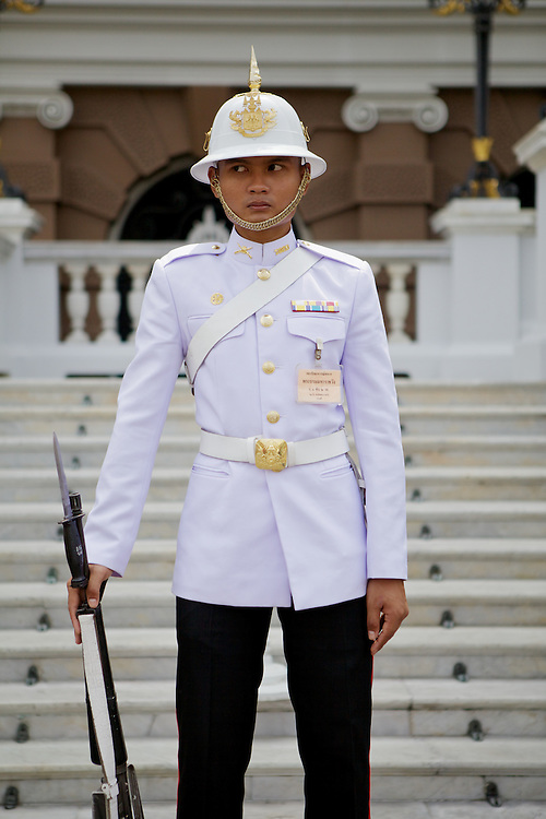 Palace guard on duty in front of the steps of the Chakri Maha Prasat hall inside the Grand Palace, Bangkok. The hall was originally the king's residence and throne hall, now houses the royal guards and a collection of ancient weapons.