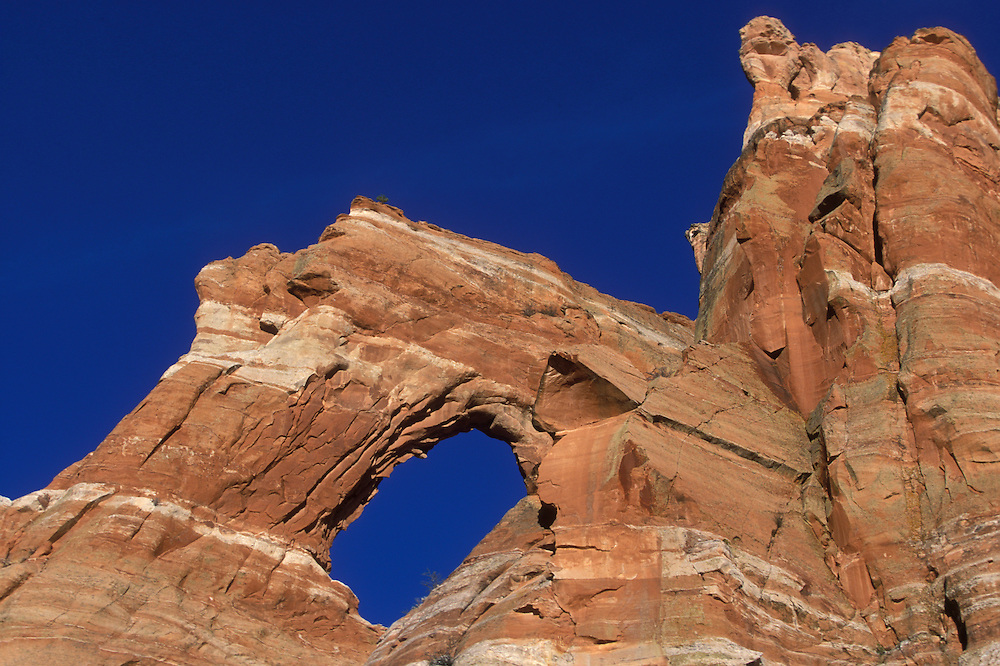 USA, New Mexico, Zuni, Natural arch in striated red sandstone cliffs near Horsehead Canyon