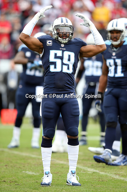 Tennessee Titans linebacker Wesley Woodyard (59) raises his arms trying to fire up the fans for a third down play during the 2015 week 7 regular season NFL football game against the Atlanta Falcons on Sunday, Oct. 25, 2015 in Nashville, Tenn. The Falcons won the game 10-7. (©Paul Anthony Spinelli)