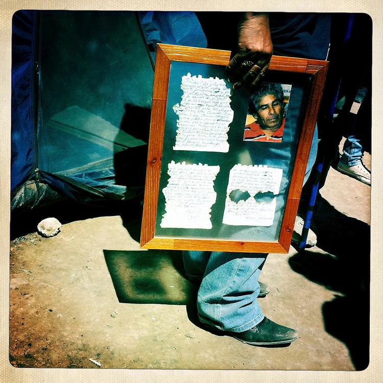 """Lillianette, esposa del Minero Mario Gomez, sostiene un cuadro con la primera carta recibida en la superficie que da cuenta de la sobrevida en las profundidades de la mina San Jose. Plan B, es un ensayo fotografico basado en aquellas cosas que la mirada somera no permite ver, de los días de espera, angustia, soledad y fe que las familias de los 33 hombres atrapados en la mina San Jose dejaron en el paisaje arido del desierto de Atacama tras el esperado rescate. """"Plan B"""", tambien es un acto de fe personal, por intentar plasmar en un relato diferente, sin más pretensión que la mirada interna a los sentimientos que esa montaña atrapó implacable y para siempre, pero que bajo la mirada superficial de los medios no permite escudriñar por tratarse de pequeños fragmentos que apelan a emociones individuales y no a la masividad que persiguen los reportes de prensa. Este ensayo es una invitación abierta a descubrir los pequeños milagros que florecieron en la montaña y en el día a día de cada una de las familias que nunca dejaron de creer en la vida, aun así se enfrentaran a la inmensidad del desierto y a las minimas espectativas de vida que el lugar entregaba.""""Plan B"""", esta constituido por fotografías ejecutadas en su totalidad con un telefono iPhone 4 y la aplicacion Hipstamatic. ROBERTO CANDIA / REVISTA NUESTRA MIRADA"""