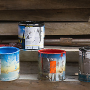 Open cans of special gondola paint on rough hewn timbers at the boatyard of D' Tramontin &amp; Figli, Venice, Italy<br />