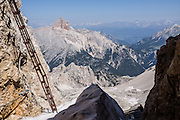 See Croda Rossa d'Ampezzo (Hohe Gaisl, 3148 meters/10,329 feet) from the start of a via ferrata route on a stairway above Rifugio Lorenzi on Monte Cristallo, in the Dolomites, Italy, Europe. Monte Cristallo lies within Parco Naturale delle Dolomiti d'Ampezzo, whose park boundary runs along the summit ridge of Croda Rossa, which also defines the border of Natural Park Fannes-Sennes-Prags. This ridge boundary also splits the Veneto region from South Tyrol (Trentino-Alto Adige/Südtirol) region of Italy. As boundaries cut it in half, Croda Rossa is often grouped in the Dolomiti di Braies (Prags Dolomites), or is sometimes considered part of the Ampezzo Dolomites. A lift to Forcella Staunies on Monte Cristallo gives unforgettable views over the mountains near Cortina d'Ampezzo. Directions: From Cortina, drive 6km east on SR48 to the large parking lot for Ski Area Faloria Cristallo Mietres (just west of Passo Tre Croci Federavecchia). Take a chair-lift from Rio Gere to Son Forca (rising from 1698m to 2215m). Then take the old style ovovia (egg-shaped) Gondellift Forcella Staunies to Rifugio Guido Lorenzi (2932m) for astounding deck views and exciting via ferrata climbing routes. UNESCO honored the Dolomites as a natural World Heritage Site in 2009.