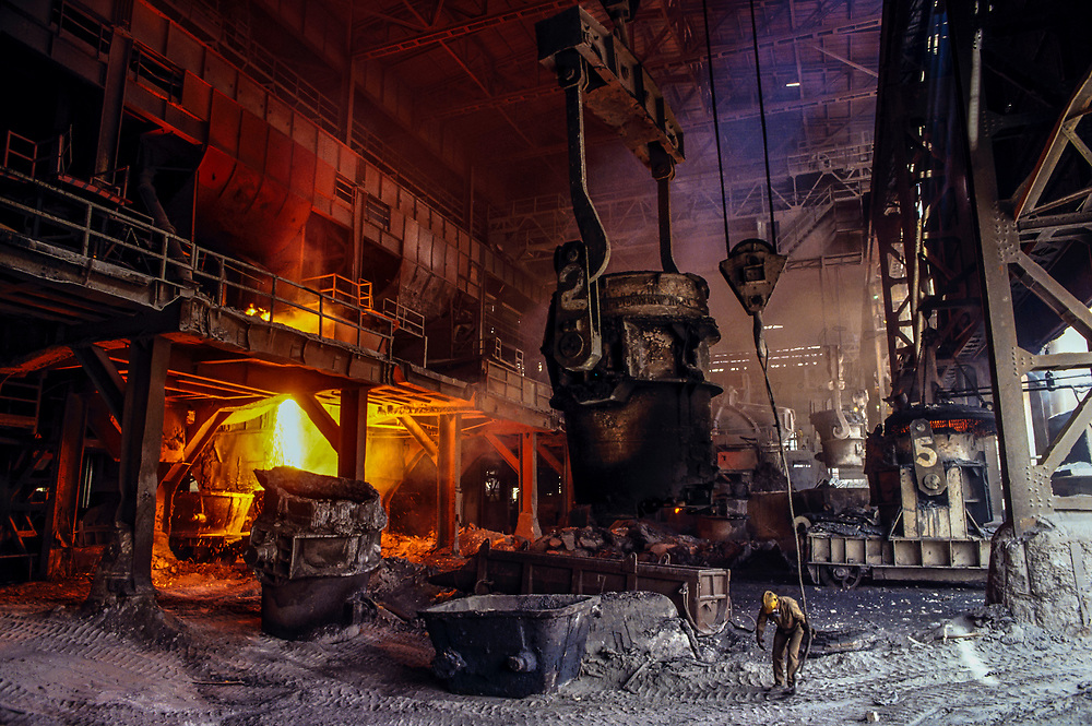 ca. 2003, Boyaca, Colombia --- A worker stands near a molten metal ladle in a steel foundry in Boyaca. --- Image by © Jeremy Horner/Corbis