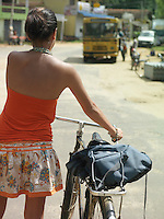 Young woman on street walking with bicycle back view